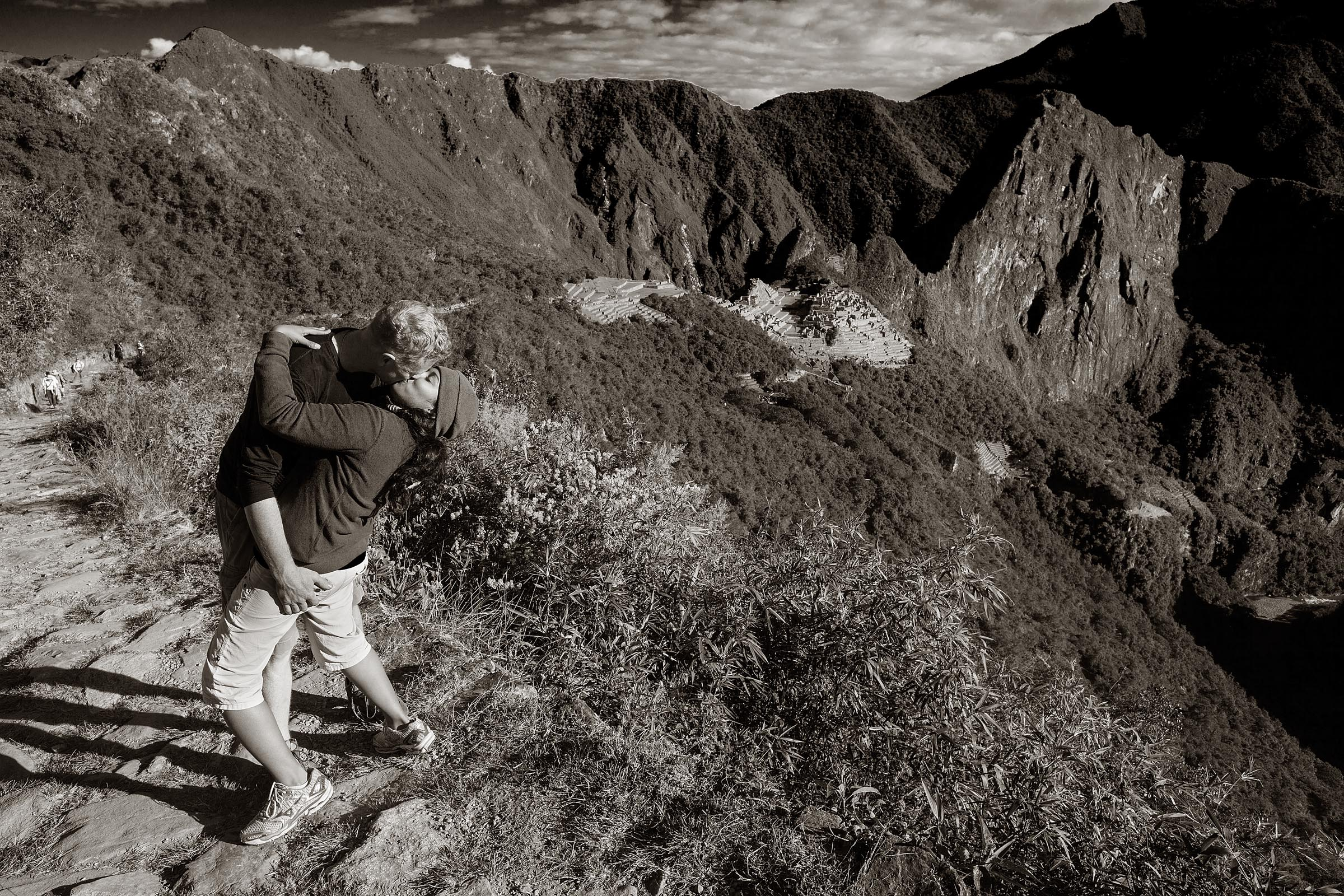 A young couple embrace in a kiss celebrating their arrival to Machu Picchu.
