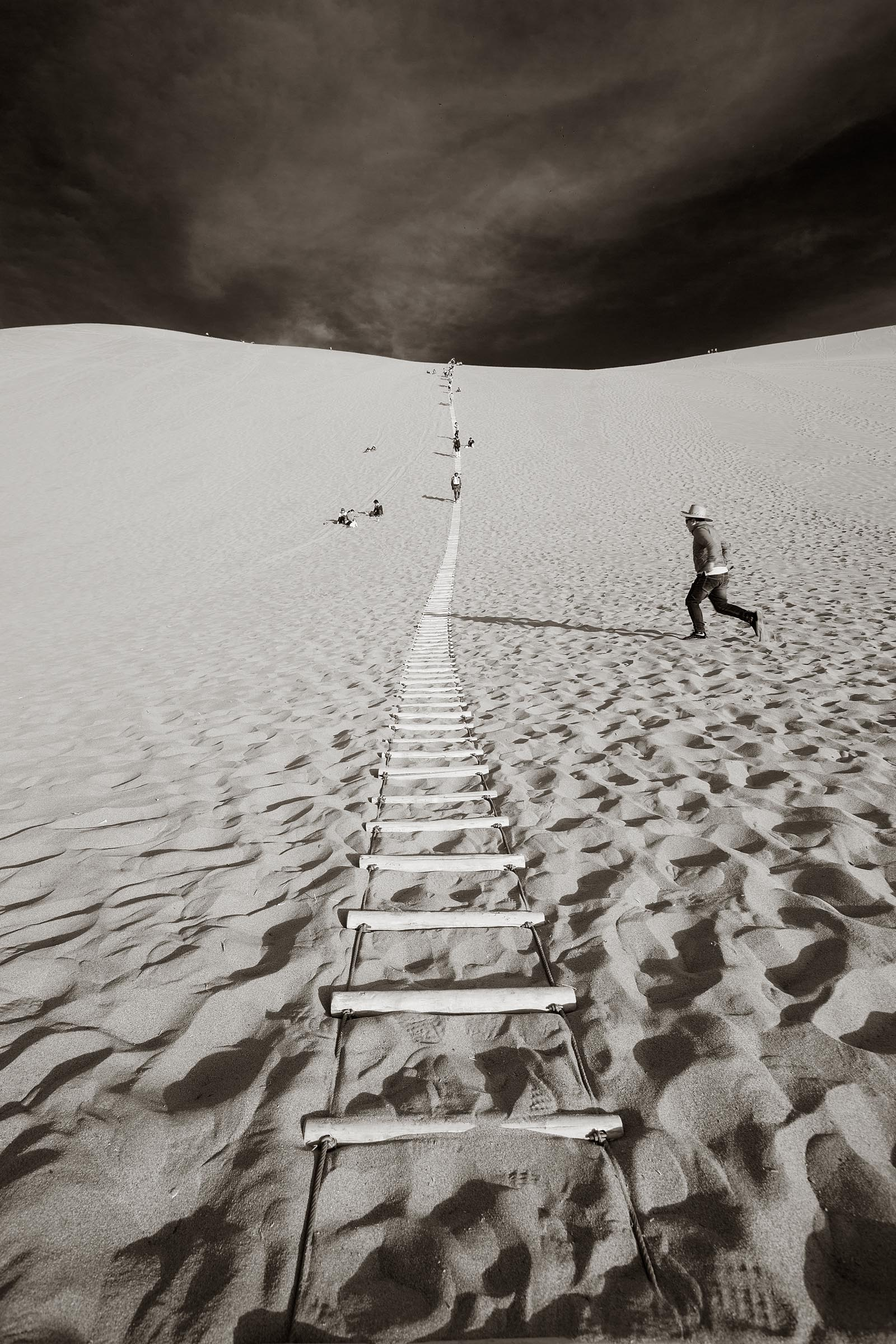 A ladder in the sand helps visitors to climb the tall sand dunes at Dunhuan.