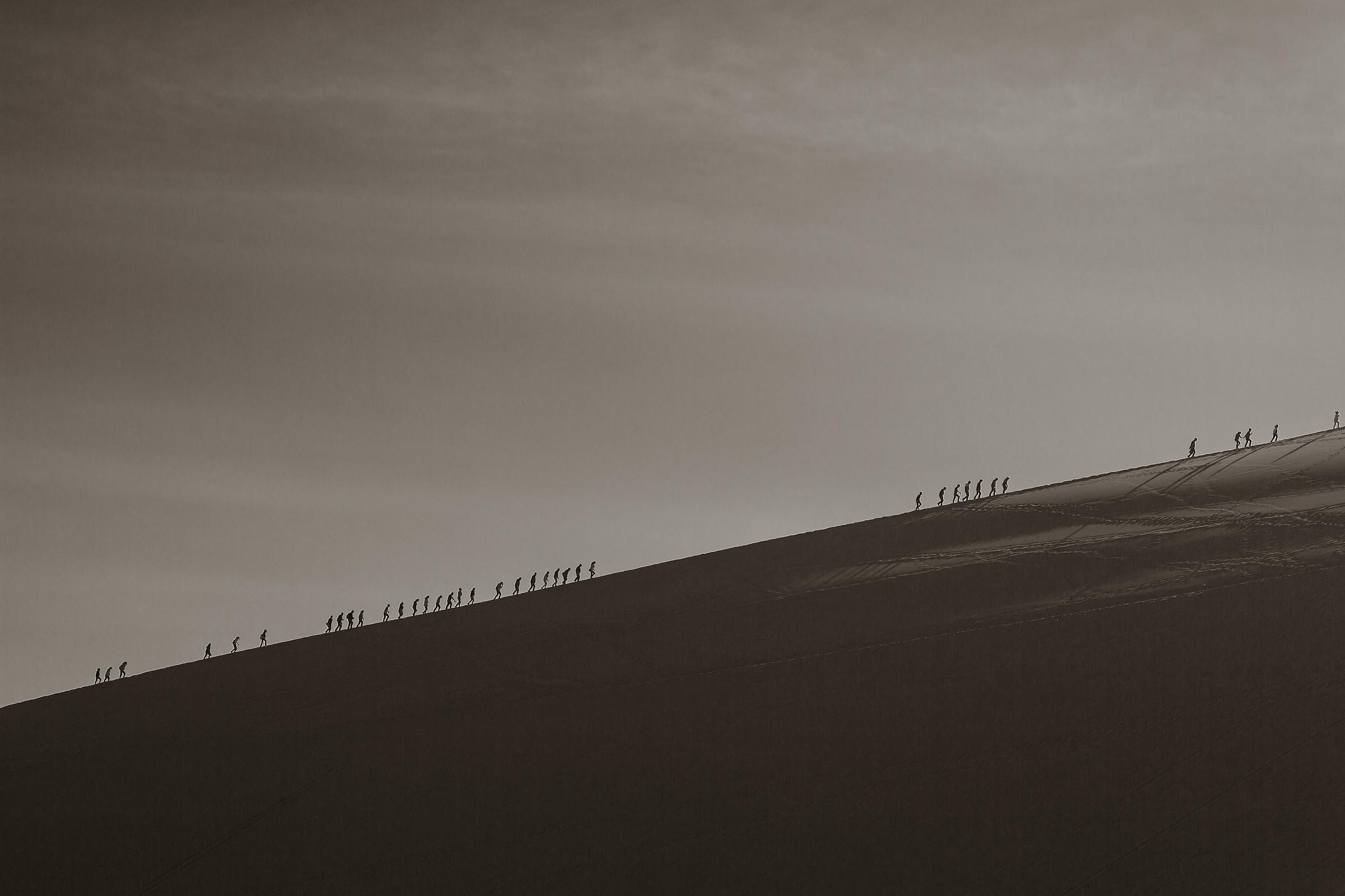 The ascent of men, women and children up large sand dune called Singing Sand Mountain in Dunhuang.