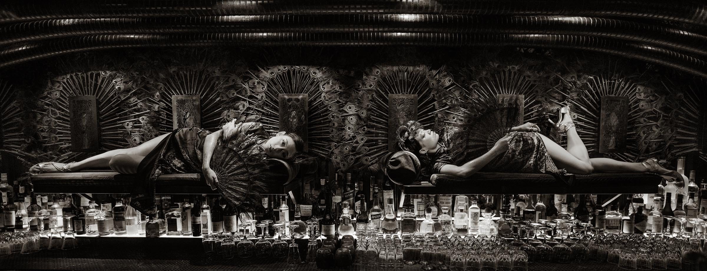 Performers lay on opium beds mounted to the wall above the bar at Ophelia.